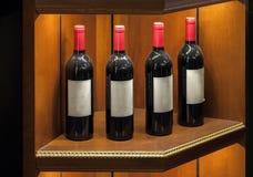 4 роскошных красных бутылки лозы на полке Стоковые Фото