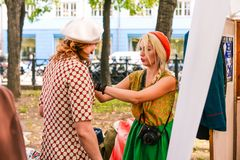 Россия, город Москва - 6-ое сентября 2014: Фотограф маленькой девочки одевает женщину для того чтобы принять фото Фотограф стоковое изображение rf