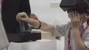 Россия, Екатеринбург - 10-ое июля 2018: Мальчик пробует шлемофон Oculus виртуальной реальности во время международной промышленно сток-видео