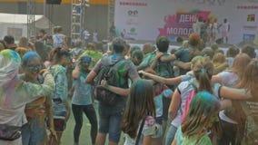 РОССИЯ, ИРКУТСК - 27-ОЕ ИЮНЯ 2018: Счастливое молодые люди танцуя и празднуя во время фестиваля Holi цветов Толпа