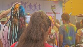 РОССИЯ, ИРКУТСК - 27-ОЕ ИЮНЯ 2018: Счастливое молодые люди танцуя и празднуя во время фестиваля Holi цветов Толпа  сток-видео