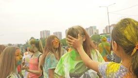 РОССИЯ, ИРКУТСК - 27-ОЕ ИЮНЯ 2018: Счастливое молодые люди танцуя и празднуя во время фестиваля Holi цветов Толпа  акции видеоматериалы