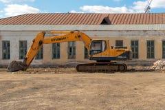Россия, Казань - 20-ое апреля 2019: Желтый экскаватор на предпосылке получившегося отказ здания стоковое фото rf