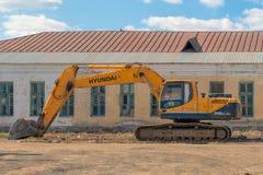 Россия, Казань - 20-ое апреля 2019: Желтый экскаватор на предпосылке получившегося отказ здания стоковое изображение