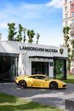 РОССИЯ, МОСКВА - 30-ое июня 2017: Автосалон Lamborghini рядом с желтым Lamborghini на красивой предпосылке неба Стоковая Фотография