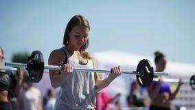Россия, Новосибирск, 2016: Девушка спорта поднимает бар к ее комоду акции видеоматериалы