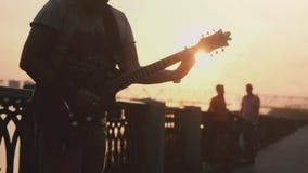 Россия, Новосибирск, 27-ое июля 2017 Закройте вверх молодых кавказских рук человека в прогулке играя гитару на изумительном заход видеоматериал