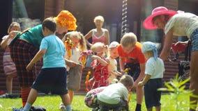 Россия, Новосибирск, 23-ье июля 2016 Жизнерадостные дети играя с аниматорами в ярких костюмах внешних на траве на Стоковая Фотография