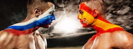Россия против Испании 2 футбольного болельщика футбола или с флагами лицом к лицу на предпосылке неба Стоковое Изображение