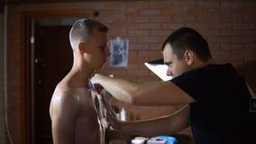 Россия, самара - 30-ое августа 2018: Профессиональный художник делает татуировку на человеке видеоматериал
