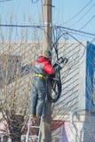 Россия, Санкт-Петербург, Nikolsky 14-ое февраля 2017 - стоящ на лестнице ремонтируя работника провода электрического Стоковое Изображение