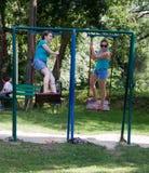 Россия, Arkhipo-Osipovka, 20-ое июня 2016: взрослое катание девушки на качании в парке ` s детей Стоковые Изображения RF