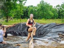 РОССИЯ, Bryansk - 30-ое июня 2018: Гонка препоны Спортсмены в костюмах скачут в яму воды стоковые изображения