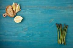 Ростки спаржи, кусков лимона и здравицы на голубом деревянном ба Стоковые Изображения RF