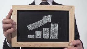 Рост вверх по графику стрелки нарисованному на классн классном в руках бизнесмена, отчете о компании сток-видео