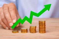 Рост в продажах и выгодах Куча лестниц монеток и зеленой стрелки указывая вверх в руки Стоковая Фотография RF