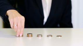 Рост дела и финансовая концепция Руки женщины положили монетки для того чтобы штабелировать сток-видео