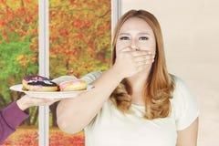 Рот женщины закрытый для donuts на плите Стоковое Фото