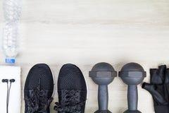 Роща фитнеса, бутылка питьевой воды, ботинки спорта, гантели, белое полотенце и наушники на деревянной предпосылке Стоковые Фото