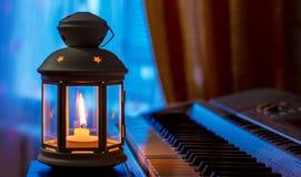 Рояль в свете фонарика со свечой Выполнять музыку с candles_ стоковая фотография