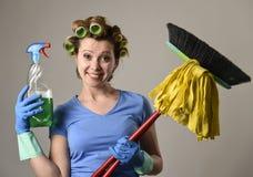 Ролики волос домохозяйки стереотипные и моя перчатки держа веник mop и бутылку брызга тензида Стоковое фото RF