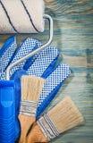 Ролик краски чистит работая перчатки щеткой на жулике взгляд сверху деревянной доски Стоковые Изображения