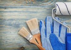 Ролик краски чистит работая перчатки щеткой на конструкции деревянной доски Стоковая Фотография RF
