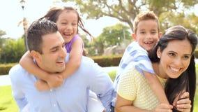 Родители давая детям езду автожелезнодорожных перевозок в парке сток-видео