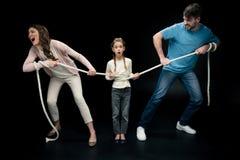 Родители вытягивая над сотрясенной дочерью с веревочкой, Стоковые Фото