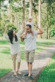 Родители в белых одеждах идя с их дочерью младенца в стоковое изображение rf