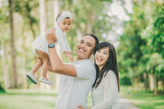 Родители в белых одеждах идя с их дочерью младенца в стоковые изображения rf