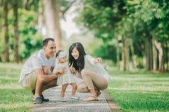 Родители в белых одеждах идя с их дочерью младенца в стоковые изображения