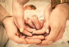 Родители держа ноги младенца в их руках Стоковое Изображение