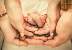 Родители держа ноги младенца в их руках Стоковые Изображения RF