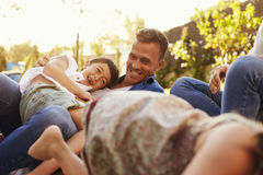 Родители играя игру с детьми на одеяле в саде Стоковое фото RF