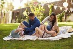 Родители играя игру с детьми на одеяле в саде Стоковые Фото