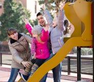 Родители играя с маленькими дочерьми на скольжении спортивной площадки Стоковое Изображение