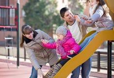 Родители играя с маленькими дочерьми на скольжении спортивной площадки Стоковые Фото