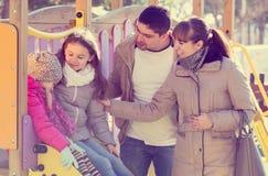 Родители играя с маленькими дочерьми на скольжении спортивной площадки Стоковые Изображения RF