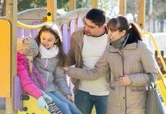 Родители играя с маленькими дочерьми на скольжении спортивной площадки Стоковые Изображения