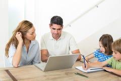 Родители используя компьтер-книжку пока красить детей Стоковые Изображения RF