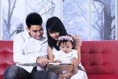 Родители используя таблетку с их дочерью стоковая фотография rf