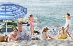 Родители и дети играть на пляже Стоковые Изображения RF
