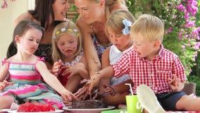 Родители и дети наслаждаясь шоколадным тортом на партии акции видеоматериалы