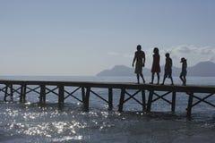 Родители и дети силуэта идя на молу Стоковое фото RF