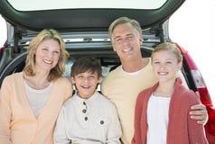 Родители и дети стоя перед открытым багажником автомобиля Стоковое Фото