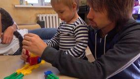 Родители и их маленький сын играя при красочная конструкция установленная совместно Концепции перемещения конструкции или железно акции видеоматериалы