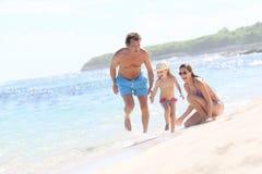 Родители и их ребенок играя совместно на пляже Стоковые Изображения RF