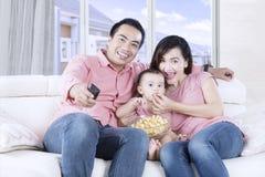Родители и ребенк смотря телевидение Стоковые Изображения RF