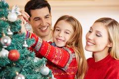 Родители и ребенок украшая рождественскую елку Стоковая Фотография